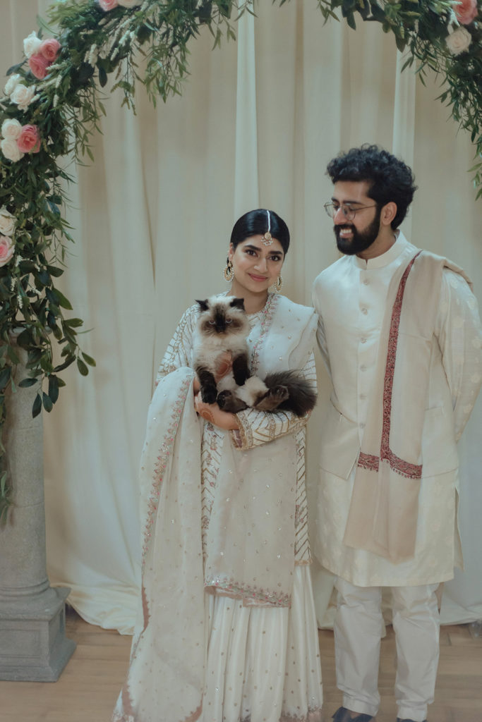 indoor wedding portrait with cat under floral arch