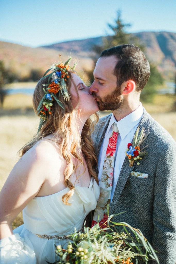 couple kissing on wedding day with flowers