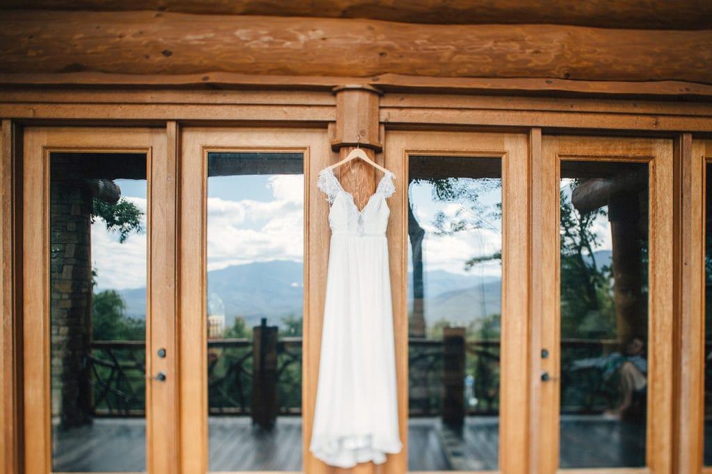 wedding dress hanging against glass doors of cabin